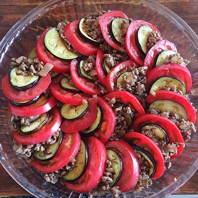 耐熱皿にトマトと茄子と挽肉の順に重ねて並べる写真