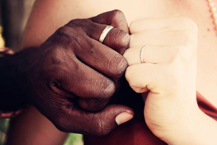 結婚指輪をしたカップルの手の写真