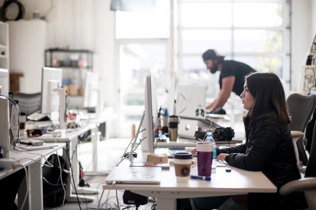 オフィスでパソコンに向かう女性と男性の画像