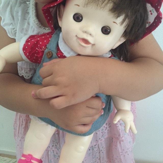 娘がぽーちゃん人形を抱えている写真